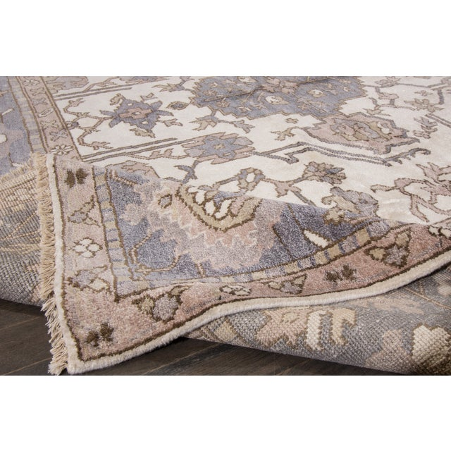A hand-knotted Oushak rug with a floral design on an ivory field. This rug has a great color scheme and is ready for in-...