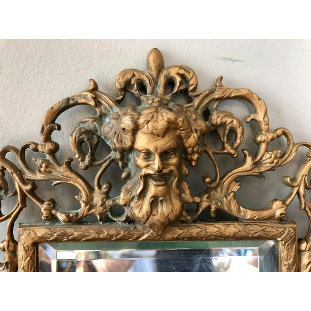 Early 20th century brass three candle mirrored sconce with Bacchus bust. Beveled mirror.
