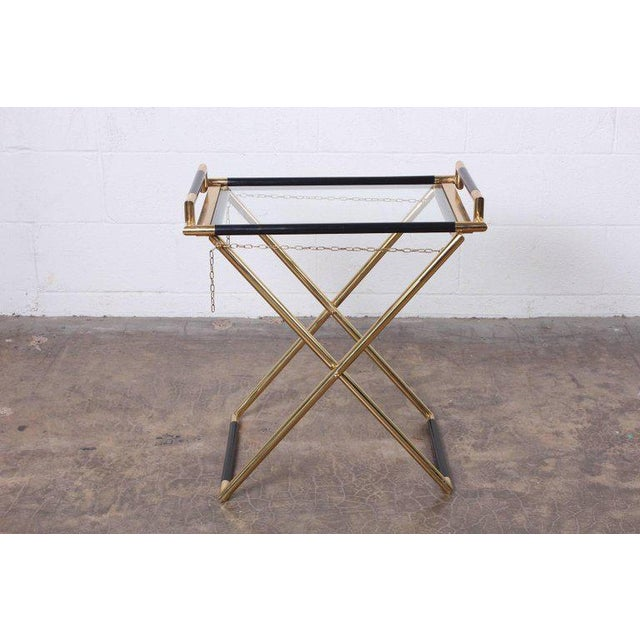 """A brass folding tray table marked """"made in italy""""."""