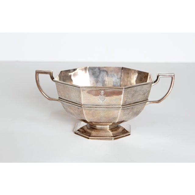An English Georgian-style sterling silver cup/bowl has an octagonal paneled and rounded form to a spreading pedestal foot....