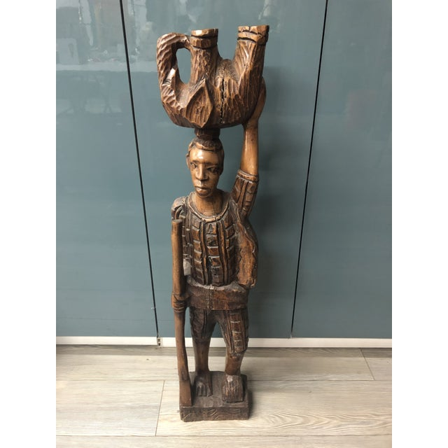 Carved by hand from a single piece of dark wood, an impressive tribal statue of a hunter holding a gun and balancing an...