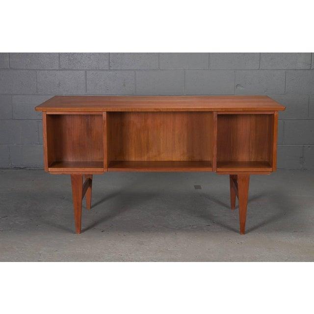 Danish modern teak desk with open cubbies on opposite side. Top drawers lock.