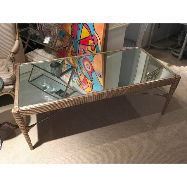 Attractive Mid-Century cocktail table with antique silver finish and mirrored top.