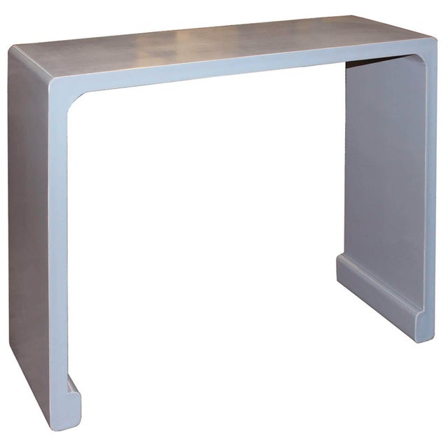 Contemporary gray lacquer waterfall console table with elegant clean lines, scroll feet and exposed wood edges.