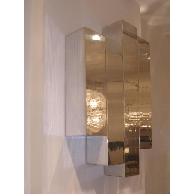 A polished aluminum wall sculpture by Cy Mann, American circa 1970's. A sculptural polished aluminum console with glass...