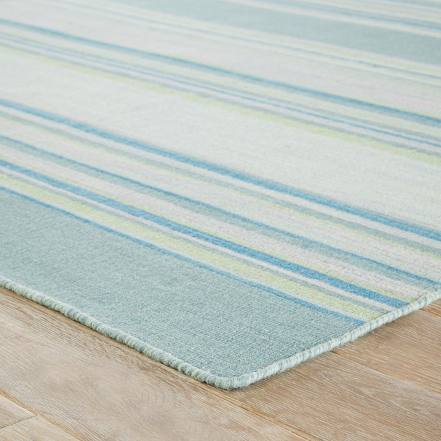 Classic with a ticking stripe, this coastal blue and turquoise flatweave area rug lends traditional charm to any space....