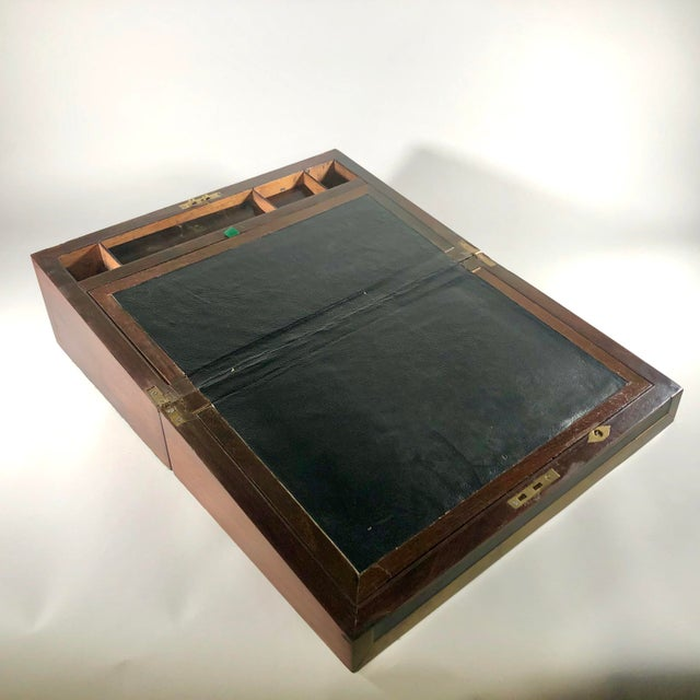 A large and fine writing box simply and elegantly decorated with rosewood and ebony veneers with brass banding and...