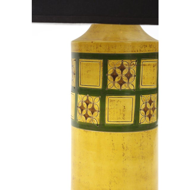 Lovely glazed ceramic lamp by Raymor, circa early 1960s. This example has hues of yellows, greens blacks and reds and sits...