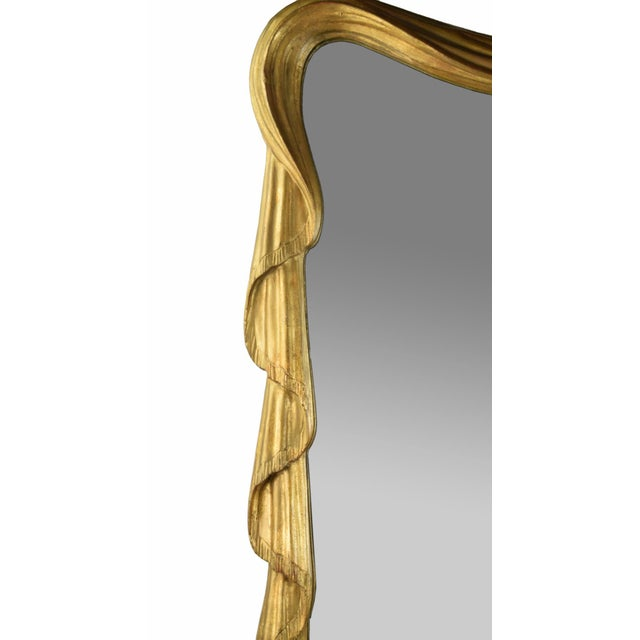 Carved and gilt wood wall mirror from Stephen Cavallo Mirrors in New York. Carved to mimic draped fabric swags. Marked on...