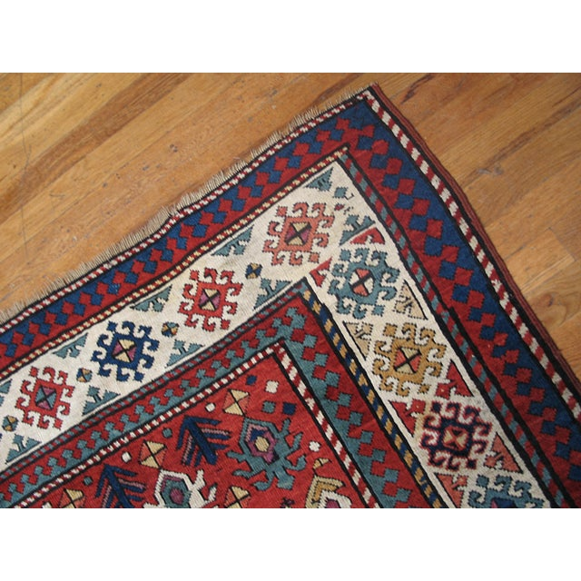 Antique Caucasian - Kazak Rug with an ivory background and patterned border.