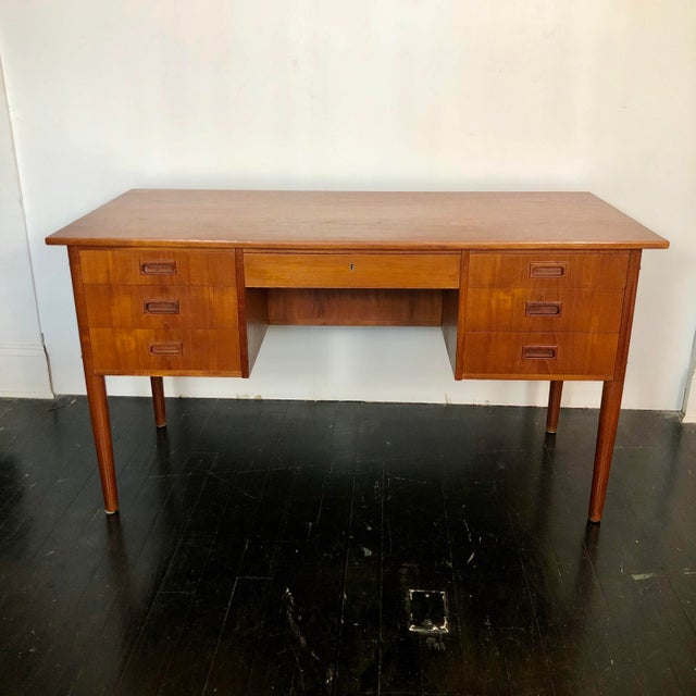 1970s Danish teak writing desk with 7 drawers and open bookcase on front. Elegant, modern lines with tapered legs.