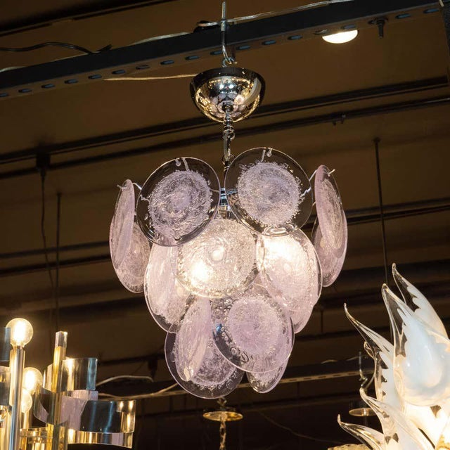 This chandelier has three descending tiers of translucent lavender discs, which are suspended from a polished chrome...