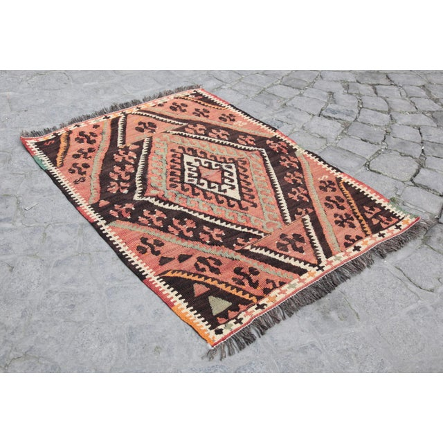 This is a vintage muted tone kilim rug from Konya, Turkey. The piece was made in the second quarter of the 20th century....