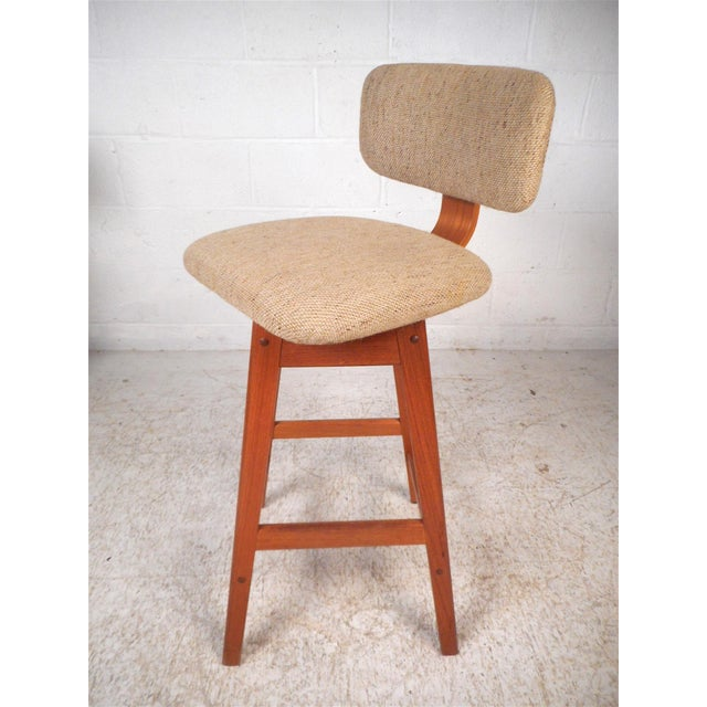 Impressive set of 3 Danish modern stools. Sleek angular Teak wood frame, swiveling seats and backrests covered in a...