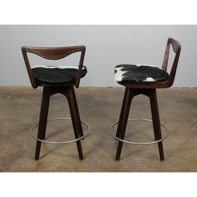 Pair of Mid Century Modern Bar Stools. Featuring swivel seats and authentic new cowhide upholstery.