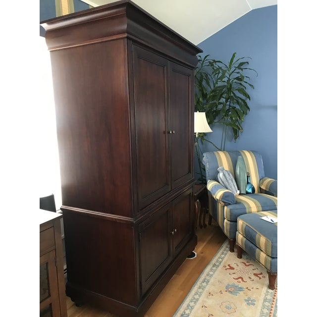 """50"""" x 27"""" x 80""""H armoire made by Hekman. Approximately 20 years old. Solid construction made of Cherry wood and brass..."""