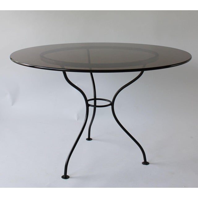 A mid-century round Iron table with tripod base and smoked glass top.