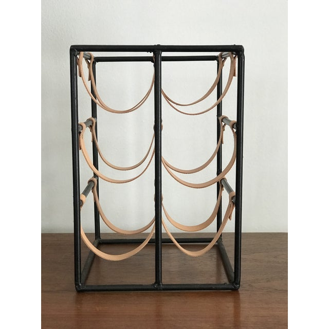 Mid-century modern six bottle wine rack. Made of wrought iron and brand new leather straps. Designed by Arthur Umanoff.