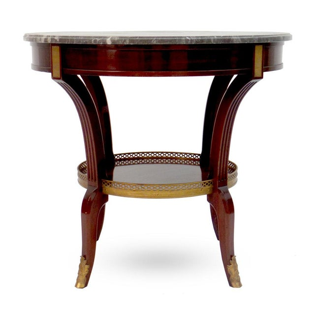 A custom Louis XVI style bouillotte table with one shelf and domestic marble top.(Can be fitted with drawer at an add'l...