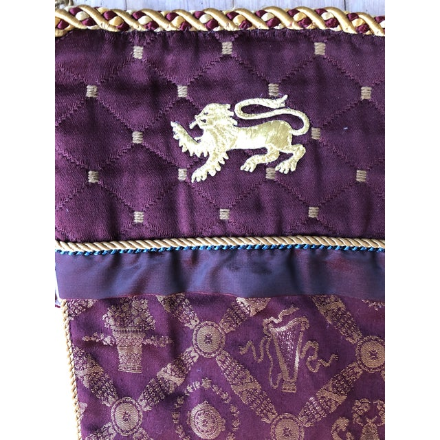 Burgundy and gold Christmas stocking with an embroidered metallic gold lion. Reverse is quilted striped solid burgundy...