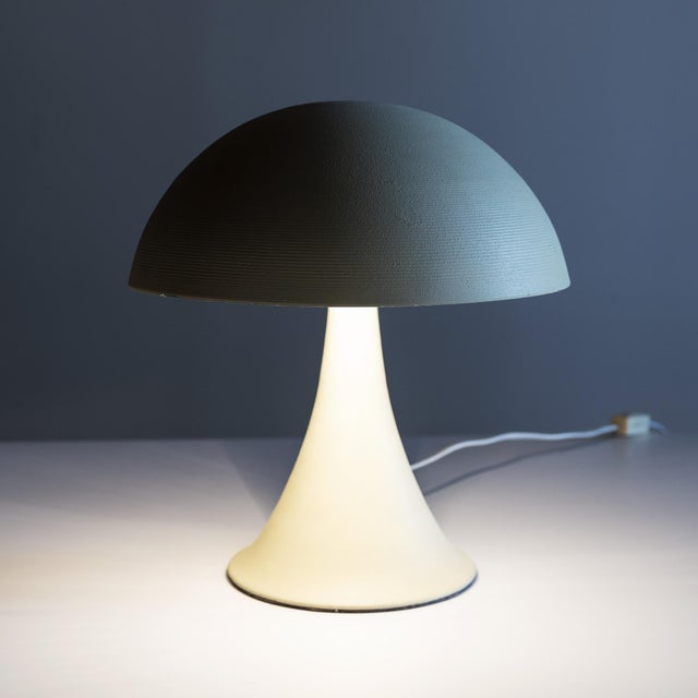 Small desk lamp, ceramic finish over metal. Shade features a subtle textured pattern of tightly spaced concentric circles....