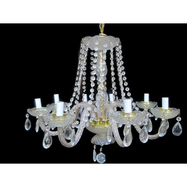 Vintage crystal, brass and encased in glass waterfall chandelier. This is a beautiful 8-arm chandelier is adorned with...