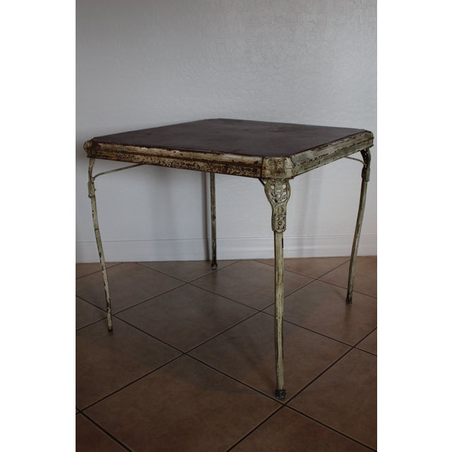 Unique Art Deco folding card table with fantastic decorative cast metal corners and upper leg pieces. Table legs are wood...