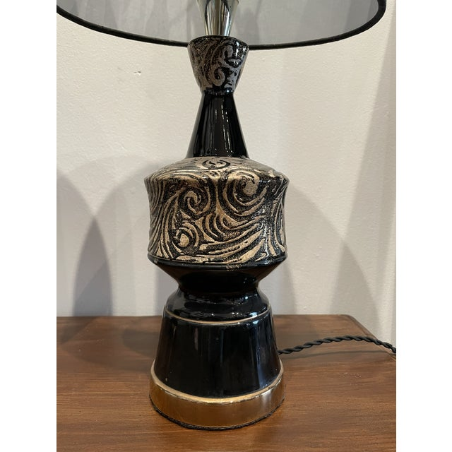 Pair of shiny black table lamps with intricate rough silver wavy patterned sections. Silver portions of these lamps...