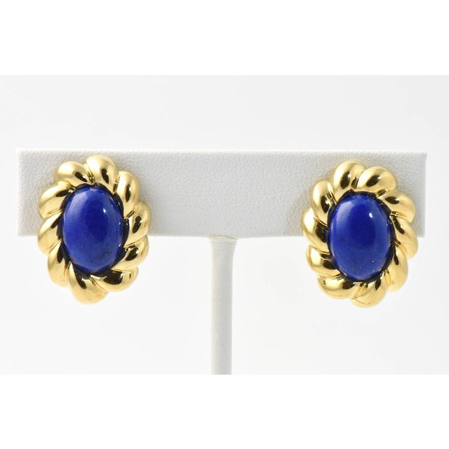 Oval cabochon lapis lazuli earrings framed in sculpted 18K gold. Clip backs. Some wear. Due to the unique nature of this...
