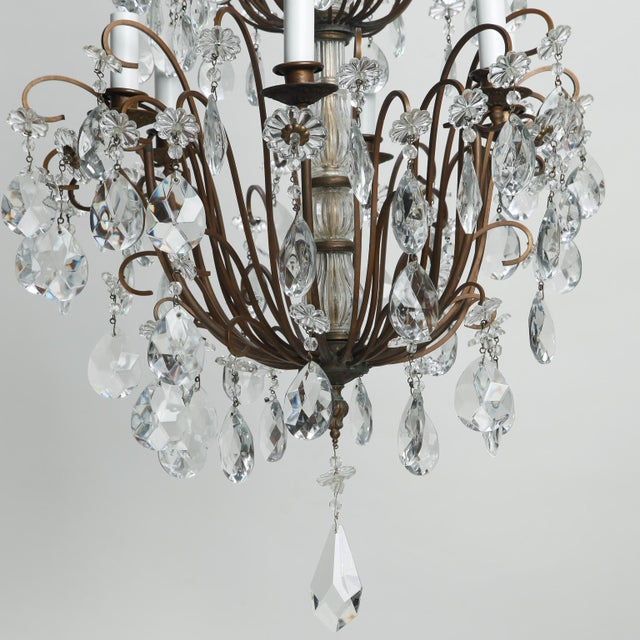 Circa 1900 tall, Italian six light chandelier has a dark metal frame and three tiers of crystal pendants and large center...