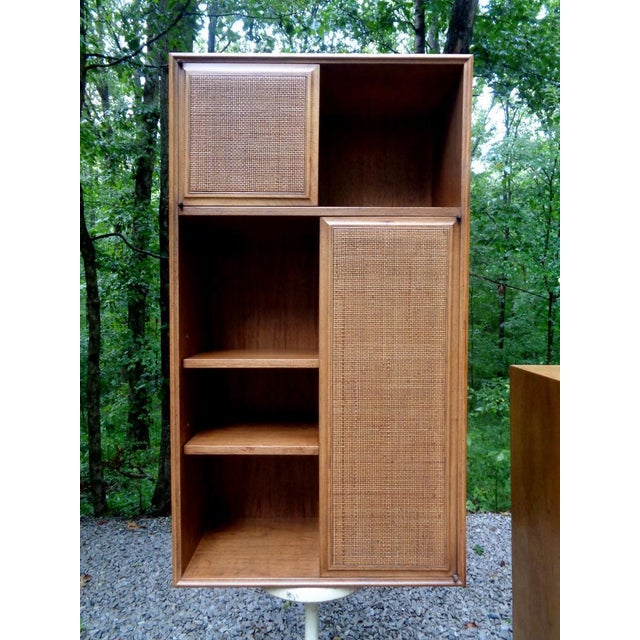 Versatile mid century wall cabinet designed by Jack Cartwright for Founders ~ c.1970. Medium brown wood grain finish with...
