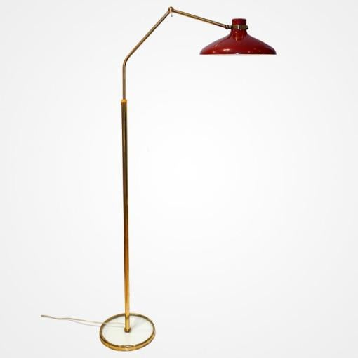 Articulated floor lamp by Fontana Arte. Jointed brass arms set with bakelite cap, brass central column in a glass base....