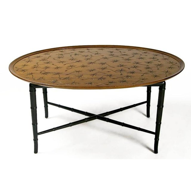 An elegant oval mahogany coffee table by Kittinger. The raised edge surrounds a flat center surface into which airborne...