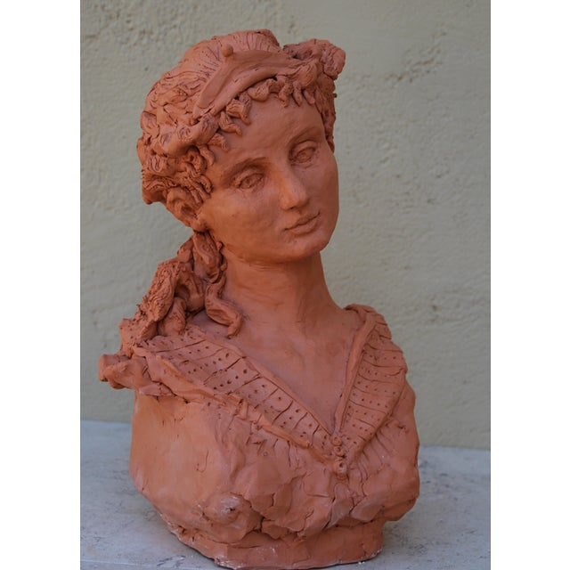 Woman's head in red terracotta. Inspired by Renaissance art. She wears a light tiara; tight ringlets edge her forehead and...