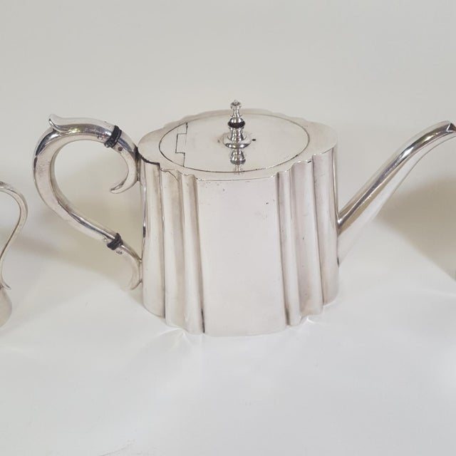 This three piece silver plate tea set was made by Thomas Wilkinson and Sons from Birmingham, UK. In 1846, Thomas's sons,...