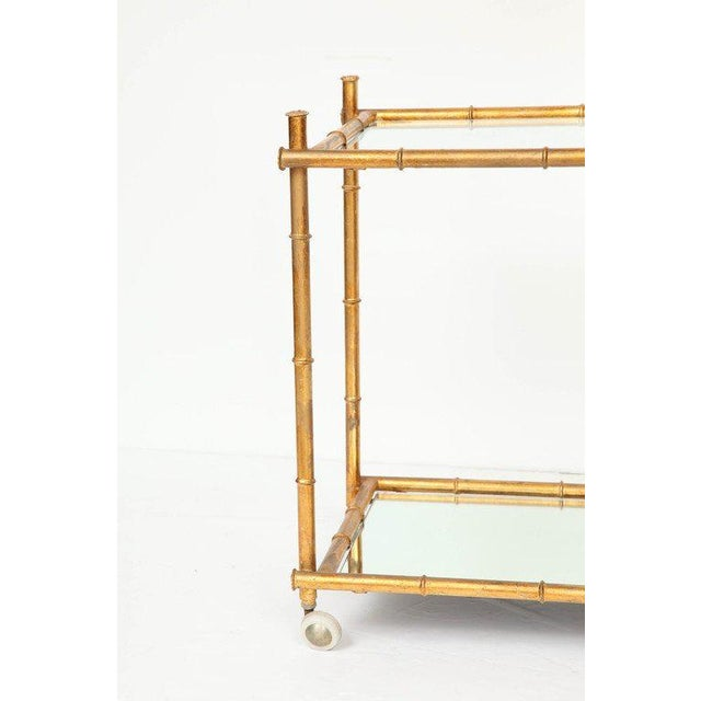 Mid-century Italian gilt metal serving/bar cart with a stylized bamboo frame and a glass and mirror shelves. Made in the...