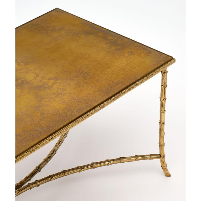 Maison Charles iconic coffee table with a gold leaf eglomised effect on the reverse of the glass top. The brass base...