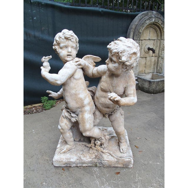 This is a pair of cast stone cupids from France. They are cast from a mold that was taken off the original statue in...