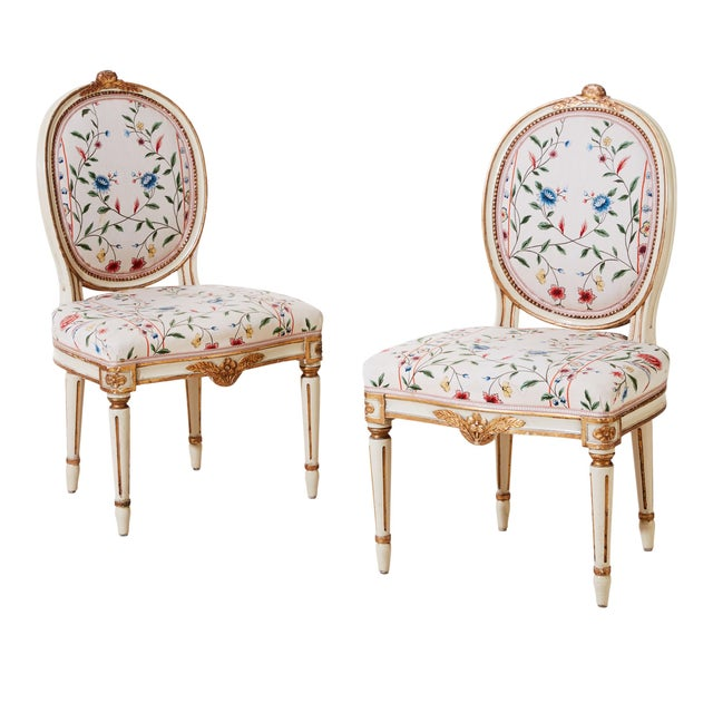 A pair of antique Gustavian chairs from the 1900's with original paint and gilding. Hand carved original details. Floral...