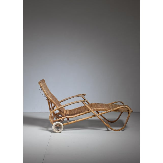 A height-adjustable chaise longue with two wheels, made of a bamboo frame with woven rattan. The backrest can be placed in...