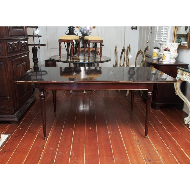 A signed, mid 20th century Maison Jansen dining table in mahogany, with rounded and tapered legs topped with a ball and...