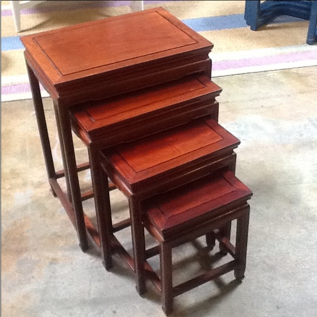 Set of four wooden Hollywood Regency-era 1940s Chinese nesting tables. Made in China for the American market.