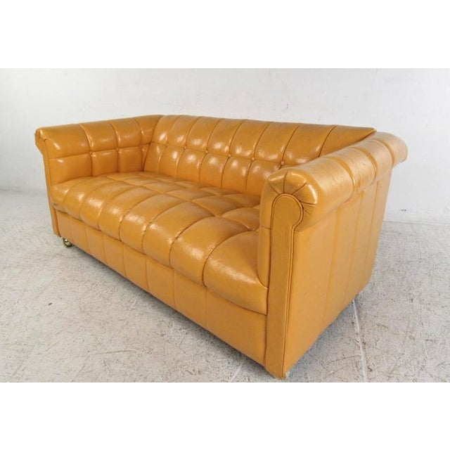 This unique vintage orange vinyl sofa features unique tufted upholstery, complimented by it's unique modern take on the...