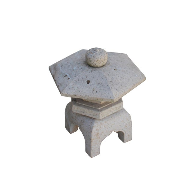 This is a garden stone lantern with a hexagon shape rooftop and simple off-white marks stone body. It is a combination of...