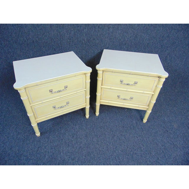 A pair of Hollywood Regency nightstands. Faux bamboo legs , cream and yellow painted finish , 2 drawers , dovetailed...