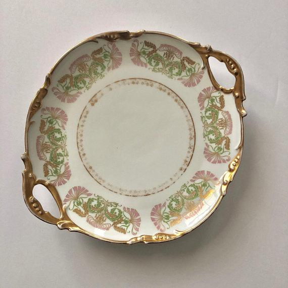 This lovely cake plate, circa 1920, was manufactured and decorated by one of the oldest family owned porcelain companies...