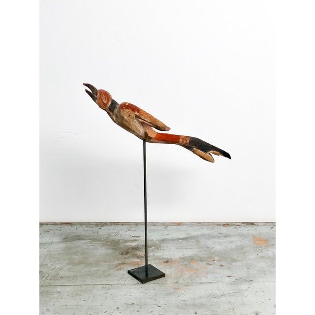 An early 20th Century New Ireland fragmentary wood and painted carving of a bird, circa 1900, on later custom steel stand.
