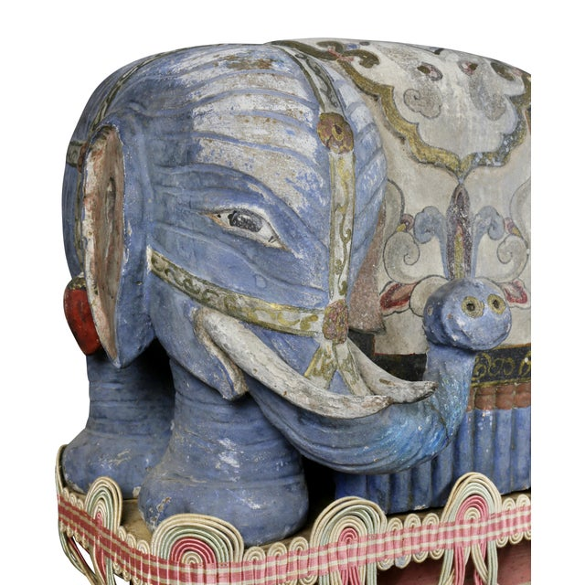 Chinese elephants on brackets. Each painted with a flat gray blue paint, bases carved wood with pink highlights and fabric...