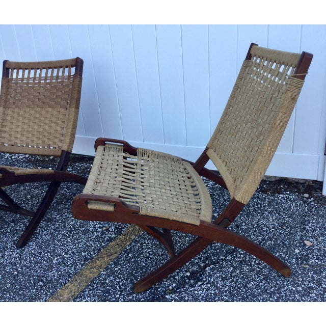Pair of Wegner-style teak and rope folding chairs hailing from Yugoslavia circa the 20th-Century. They feature a woven...