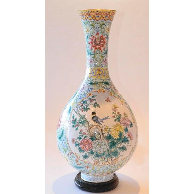Vintage Chinese enamel bottle vase on wood stand. Vase features two panel enamel on brass design depicting elegant flora...
